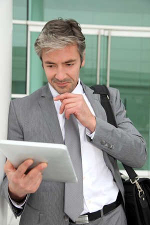 modernity: Businessman standing outside building with electronic tablet