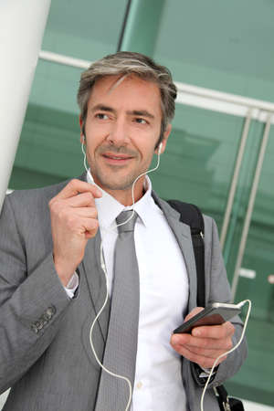 earphone: Businessman talking on mobile phone with handsfree headset Stock Photo