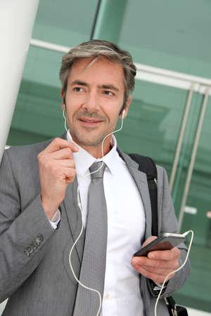 mobile headset: Hombre de negocios hablando por tel�fono m�vil con el auricular manos libres Foto de archivo