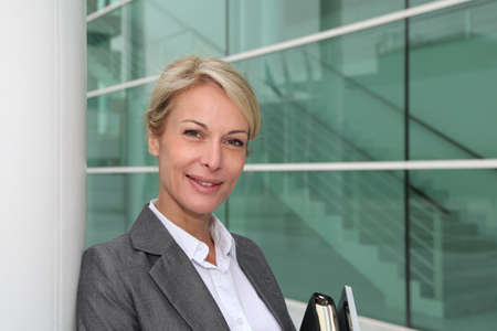Mature businesswoman standing in front of modern building photo