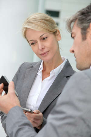 exchanging: Business people exchanging phone numbers