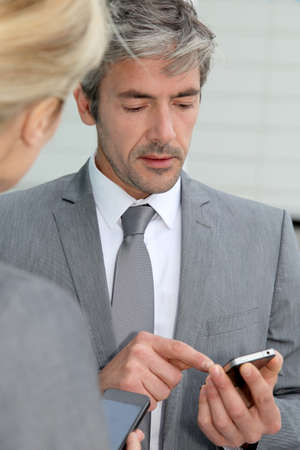 Business people exchanging phone numbers photo