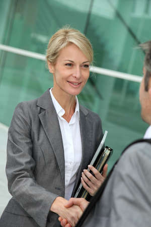 Closeup of sales woman shaking hand to business patner photo