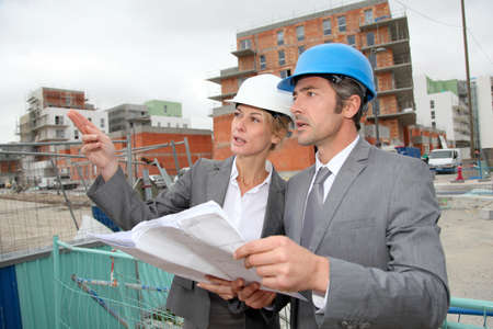 female engineer: Construction engineers checking plan on building site