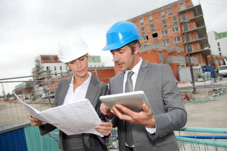 Construction engineers checking plan on building site Stock Photo - 14023970