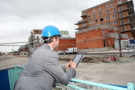 building site: Architect using electronic tablet on building site