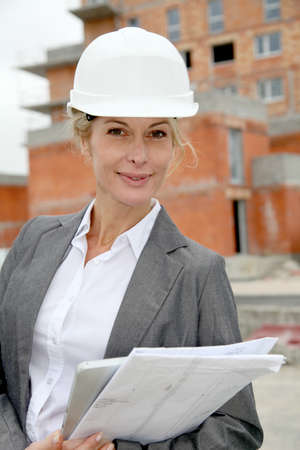 Woman engineer standing in front of building site photo