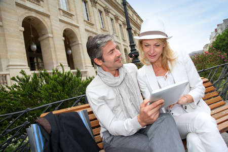 Trendy couple using electronic tablet on city bench photo
