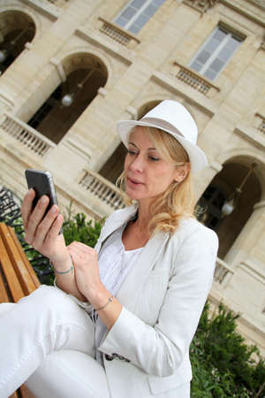 Modern woman in town using mobile phone photo