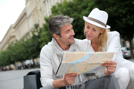 senior adult woman: Middle aged couple looking at city map