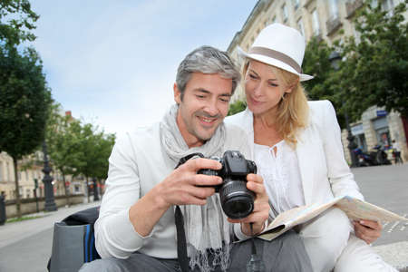 season photos: Happy tourists looking at pictures on camera screen Stock Photo