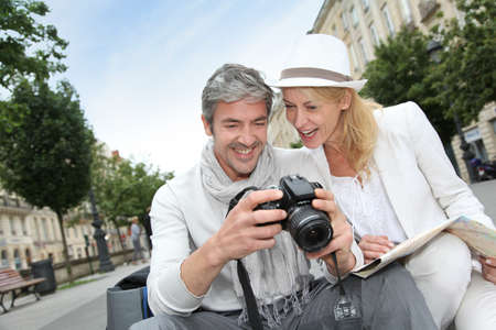 Happy tourists looking at pictures on camera screen photo
