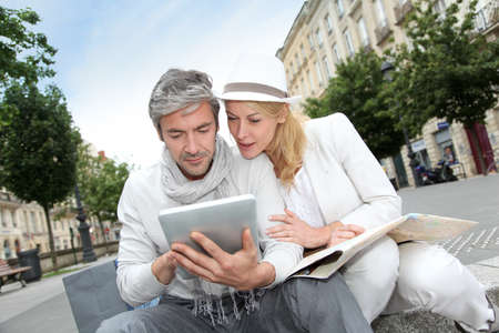 Couple visiting city with help of map and electronic tablet photo