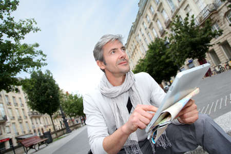 40s adult: Cheerful handsome guy in town using electronic tablet Stock Photo