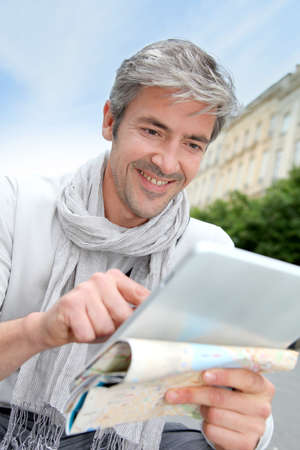 Cheerful handsome guy in town using electronic tablet photo
