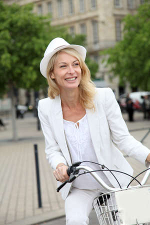 Cheerful middle aged woman riding bike in town photo