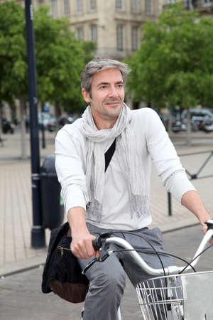 Trendy guy riding bike in town photo