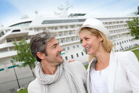tourists stop: Happy romantic couple standing in front of cruise boat