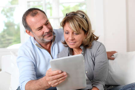 Senior couple looking at web pages on electronic tablet Stock Photo - 14023638