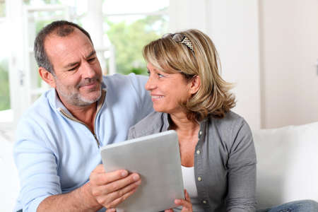 Senior couple looking at web pages on electronic tablet photo