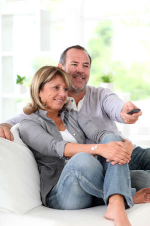 Senior couple watching television at home photo