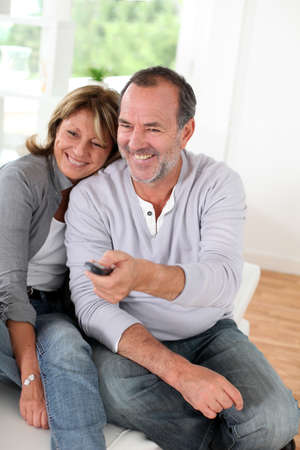 Senior couple watching televion at home photo