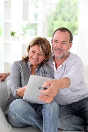 Senior married couple choosing movie on tv photo