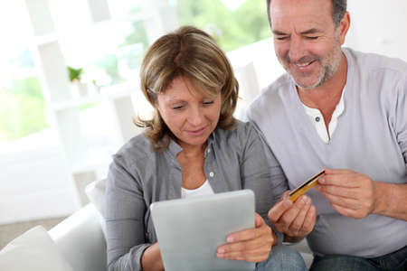 Senior couple using credit card to shop online Stock Photo - 14023063