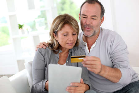 Senior couple using credit card to shop online photo