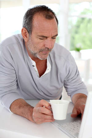 Senior man connected on internet with laptop at home photo