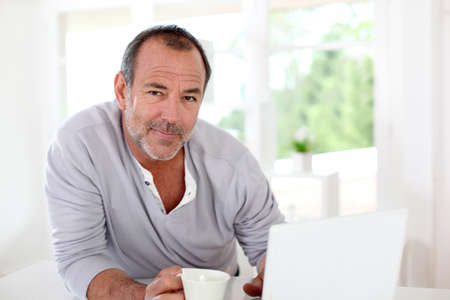 resting: Senior man connected on internet with laptop at home Stock Photo