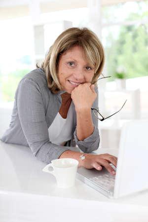 old technology: Senior donna di fronte al laptop con una tazza di caff�