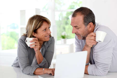 Senior couple drinking coffee in front of laptop computer photo