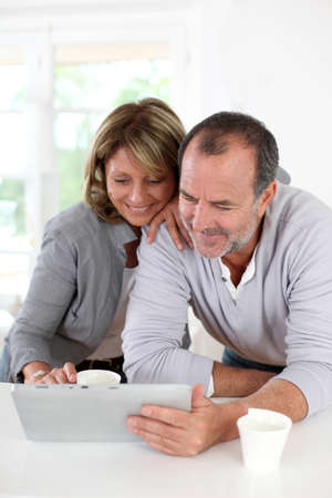 Senior couple drinking coffee in front of tablet photo