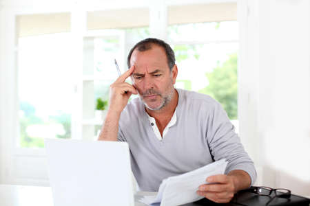 old man portrait: Senior man being puzzled with tax documents