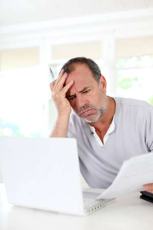 Senior man being puzzled with tax documents photo