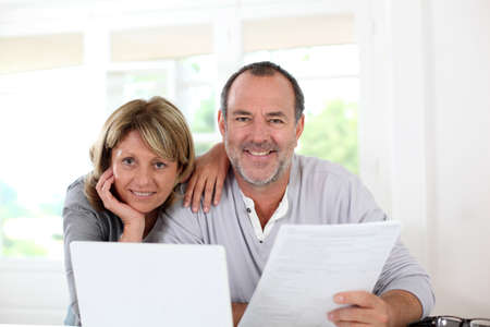 declaring: Senior couple at home declaring income on internet