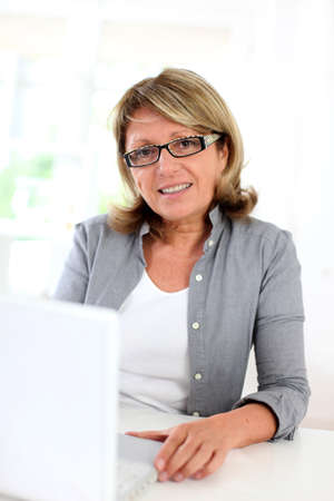 Senior businesswoman sitting in front of laptop computer