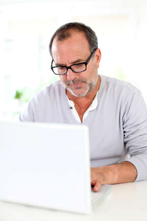 Senior businessman working on laptop from home photo