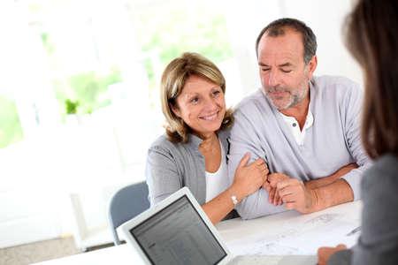 agente: Anziano, coppia, pronto a comprare un nuovo contratto di lettura casa Archivio Fotografico