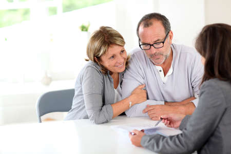 financial planning married: Senior couple signing financial contract