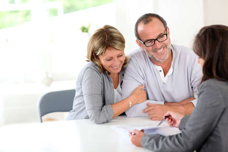 real estate planning: Senior couple signing financial contract