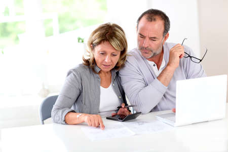Couple reading construction plan at home with use of laptop photo