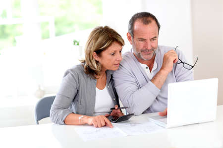 construction plans: Couple reading construction plan at home with use of laptop Stock Photo