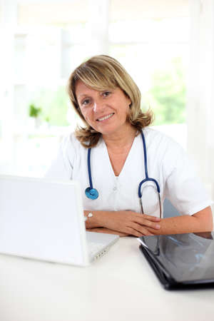 Portrait of mature nurse sitting at her desk photo