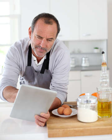 Senior man in kitchen using electronic tablet photo