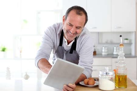 Senior man in kitchen using electronic tablet photo