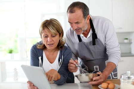 Senior couple having fun in home kitchen photo