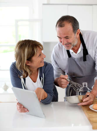 Senior couple having fun in home kitchen Stock Photo - 14022676