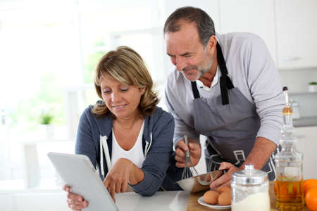 Senior couple having fun in home kitchen photo